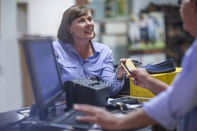 Woman buying shoes paying with credit card — Stock Photo
