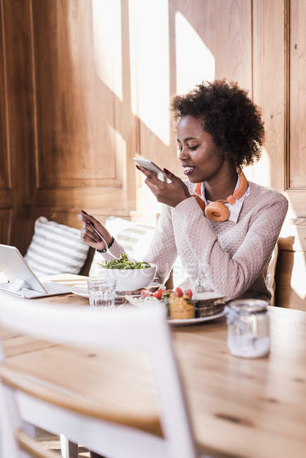 Young woman using cell phone and tablet while eating in a cafe — Stock Photo