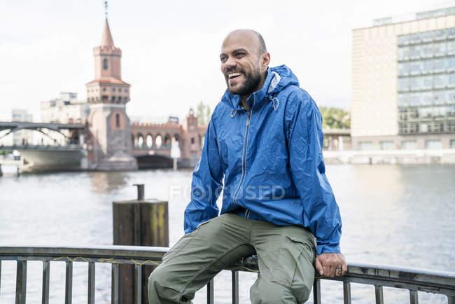 Alemanha, Berlim, homem rindo vestindo rainjacket azul sentado no corrimão em frente à Ponte Oberbaum — Fotografia de Stock