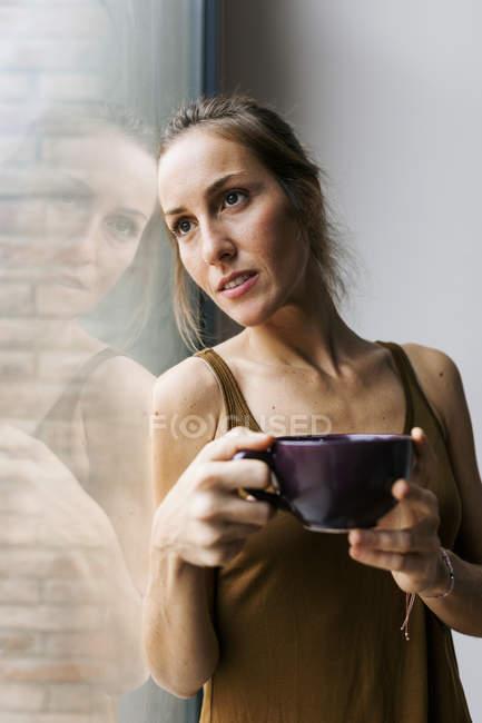 Женщина смотрит из окна, пить кофе — стоковое фото