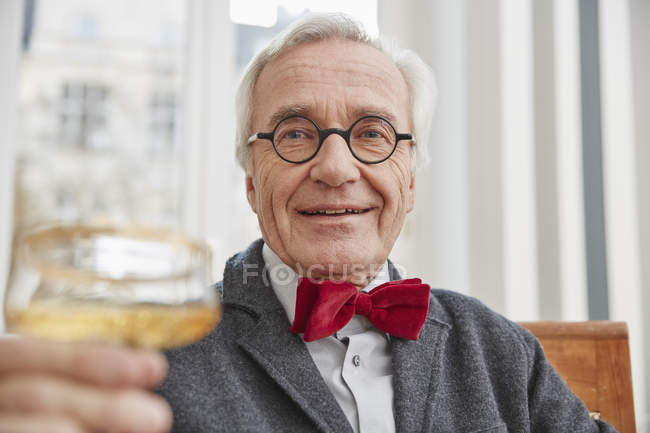Senior man raising champagne glass — Stock Photo