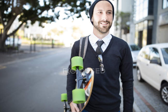 Young man wearing beanie holding skateboard — Stock Photo
