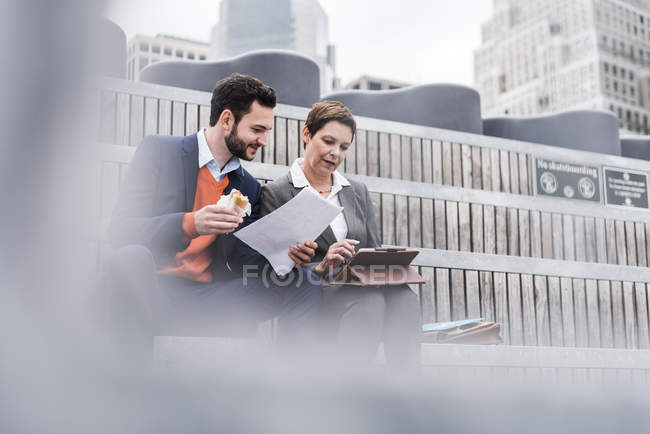 Business people meeting outdoor, man holding a sandwich — Stock Photo