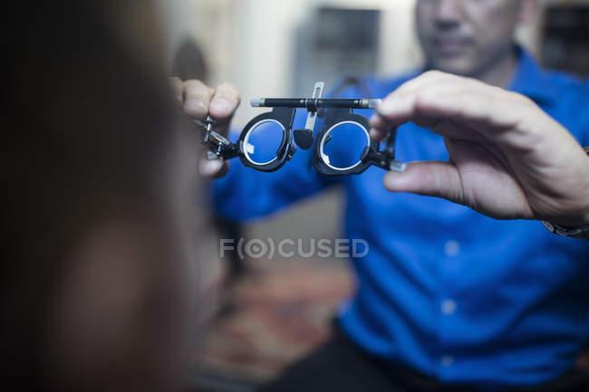 Optometrist holding test frames for girl in medical clinic — Stock Photo