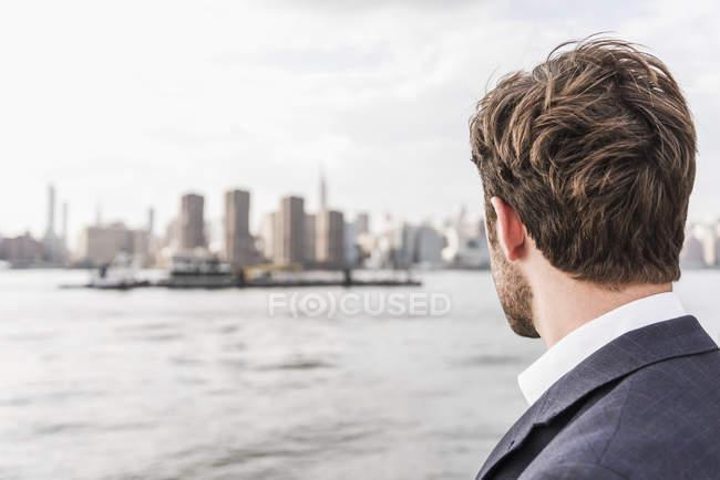 Uomo a East River guardando Manhattan, New York, Stati Uniti — Foto stock