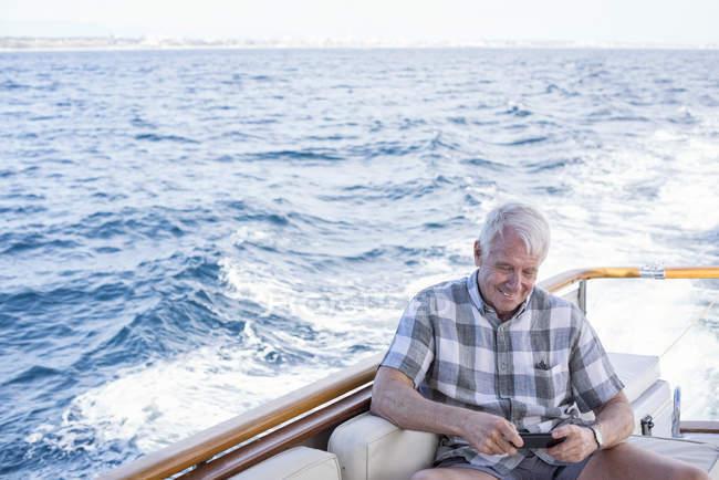 Homem sênior em um passeio de barco usando telefone celular — Fotografia de Stock