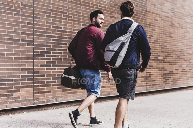 Два друга со спортивными сумками идут по тротуару — стоковое фото