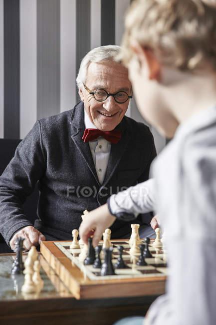 Abuelo y nieto jugando al ajedrez en casa - foto de stock