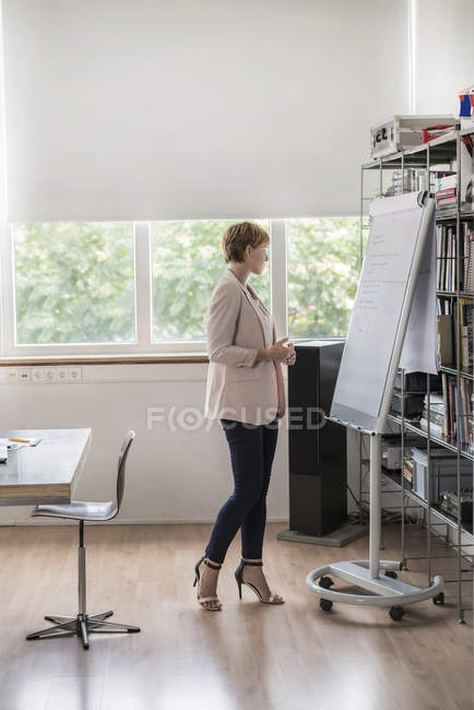 Businesswoman standing at flipchart in modern conference room — Stock Photo