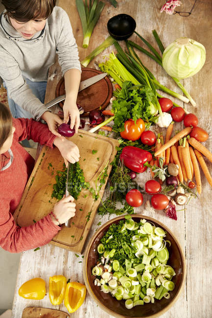Boy and girl chopping vegetables in the kitchen, top view — Stock Photo