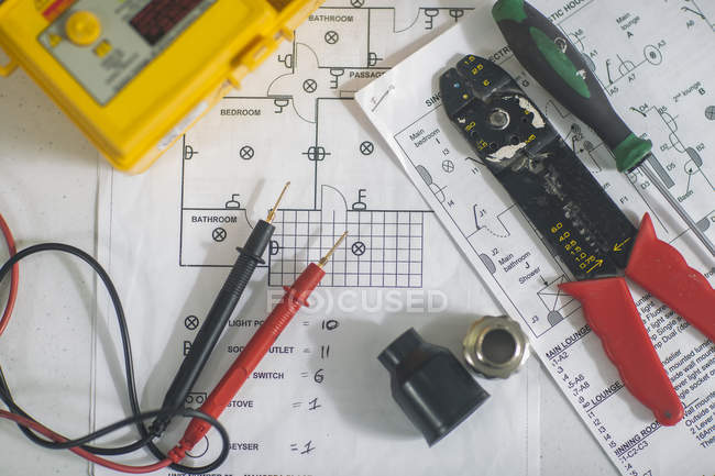 Top view of different electrician tools on schemes and plans — Stock Photo