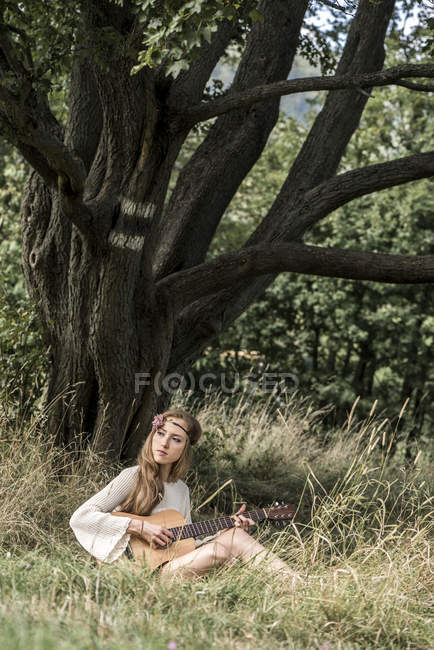 Young woman playing guitar at tree — Stock Photo