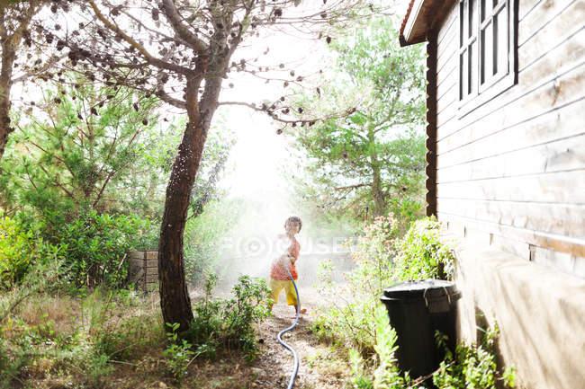 Niño jugando con manguera de jardín - foto de stock