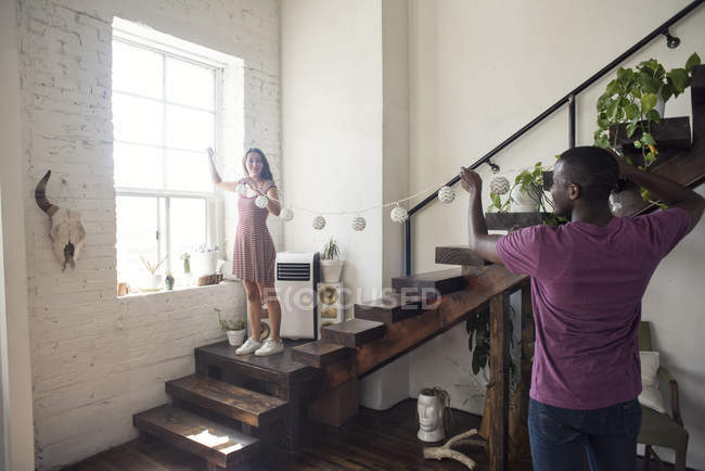 Young couple decorating loft with fairylights — Stock Photo