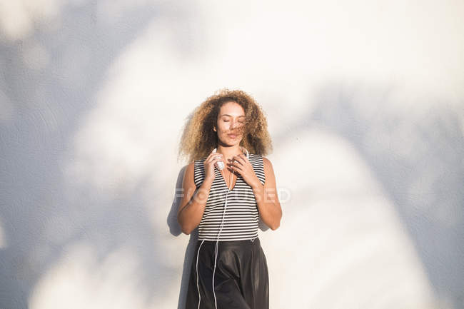Young woman with eyes closed leaning against wall at sunlight — Stock Photo