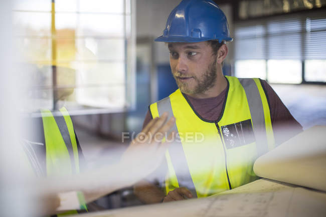 Construction worker wearing working clothes talking to colleague — Stock Photo