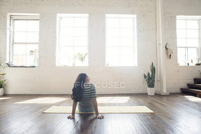 Giovane donna che si siede sul tappeto in appartamento loft vuoto — Foto stock