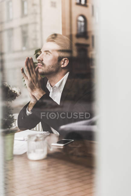 Young businessman thinking in a cafe behind windowpane — Stock Photo