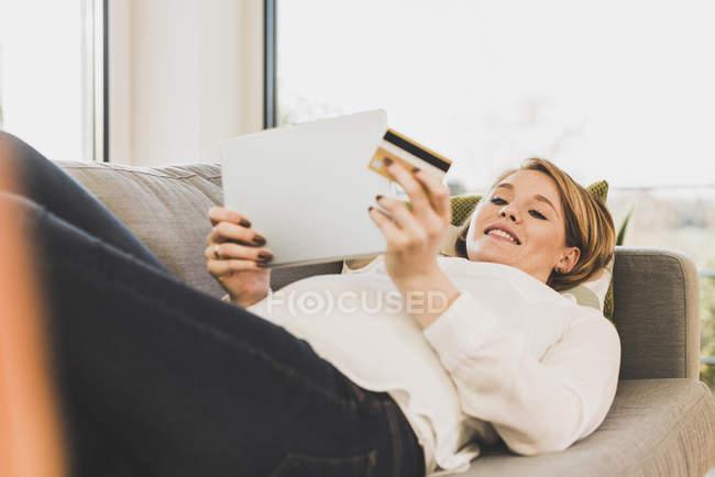 Sourire femme enceinte sur le canapé shopping en ligne — Photo de stock