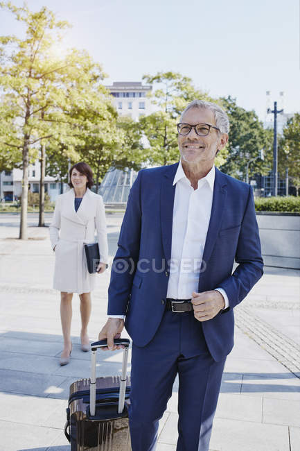 Smiling businessman on the go with businesswoman in background — Stock Photo