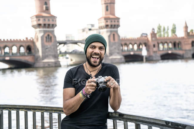 Germany, Berlin, portrait of happy man with camera standing in front of Oberbaum Bridge — Stock Photo