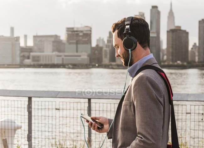 Молодой человек с наушниками и мобильным телефоном в Ист-Ривер, Нью-Йорк, США — стоковое фото