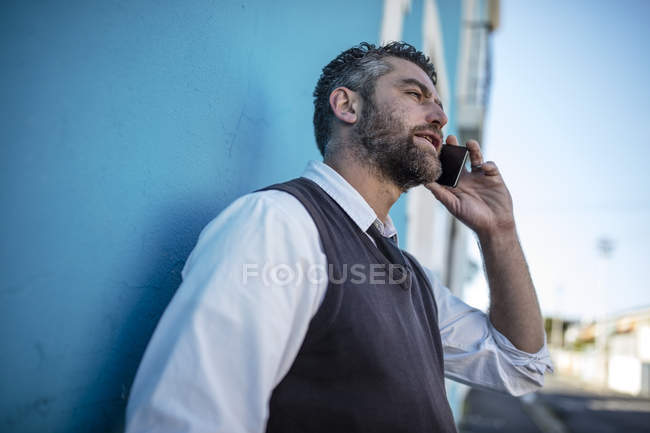 Man leaning against blue wall talking on cell phone — Stock Photo