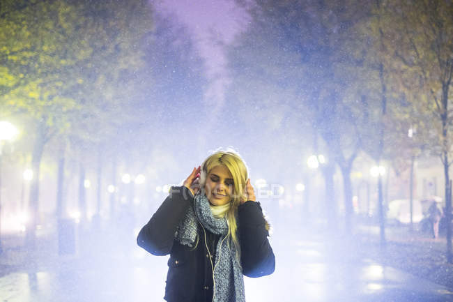 Young woman listening music with headphones at hazy night — Stock Photo
