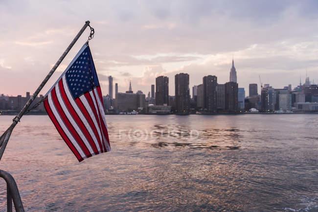 USA, New York City, uns Flagge auf Fähre auf dem East River mit Skyline von Manhattan im Hintergrund — Stockfoto