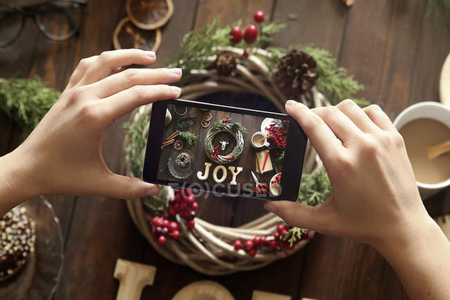 Woman's hands taking picture of self-made Advent wreath with smartphone — Stock Photo
