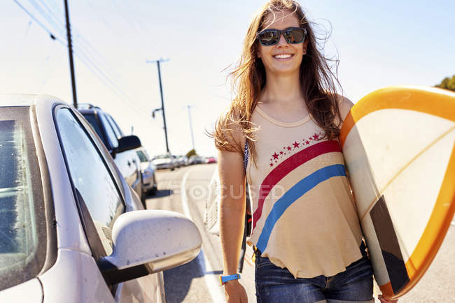 Smiling young woman carrying surfboard on coastal road — Stock Photo