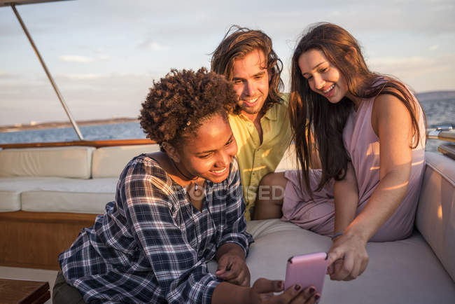 Friends on a boat trip with cell phone — Stock Photo