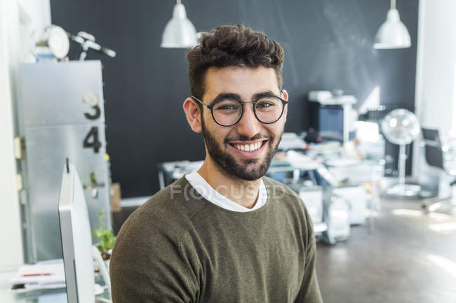 Portrait of smiling man with glasses standing in modern office — Stock Photo