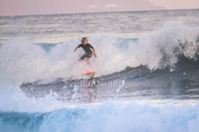 Teenager boy riding on surfboard at waving ocean — Stock Photo