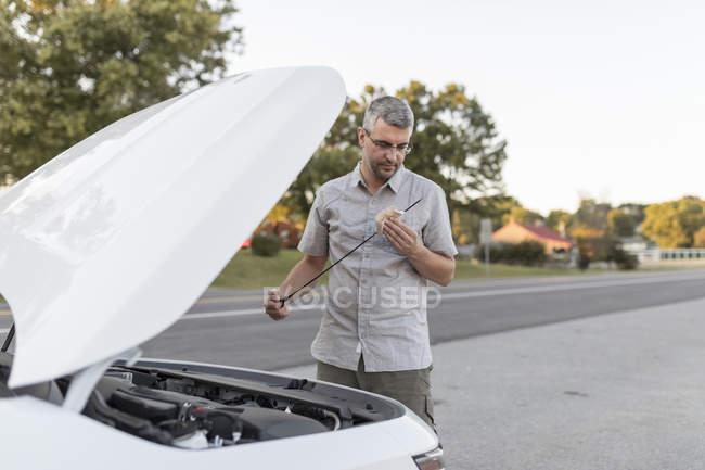 Человек, проверка уровня масла на обочине дороги — стоковое фото
