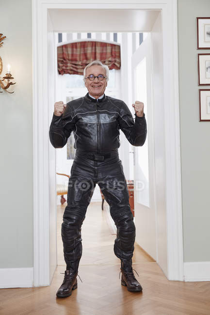 Happy senior man in motorcycle suit at home — Stock Photo