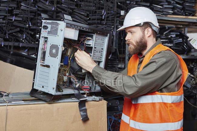 Travailleur dans l'usine de recyclage informatique démontage bureau pc — Photo de stock