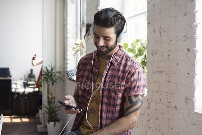 Усміхаючись молода людина в навушниках, дивлячись на мобільний телефон в лофт — стокове фото