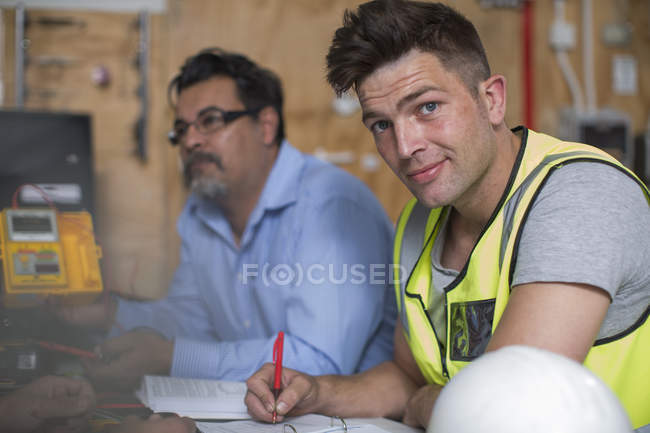 Confident young man attending an electrician workshop — Stock Photo