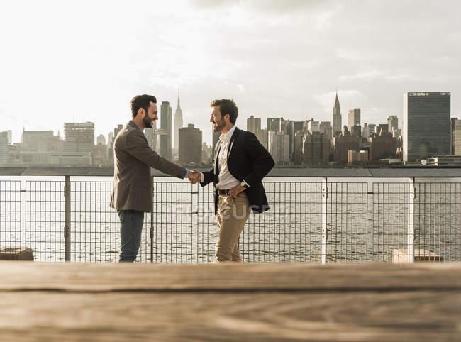 Zwei Geschäftsleute beim Händeschütteln am East River, New York City, USA — Stockfoto