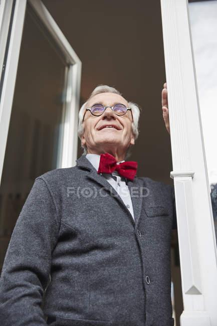 Smiling senior man at the window — Stock Photo