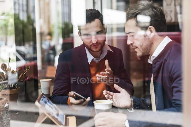 Reunión de empresarios en cafetería y uso de dispositivos móviles - foto de stock