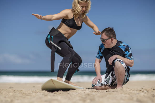 Teenage boy with down syndrome having surf lessons with woman on beach — Stock Photo