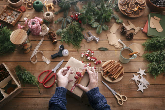 Woman's hands decorating Christmas present — Stock Photo