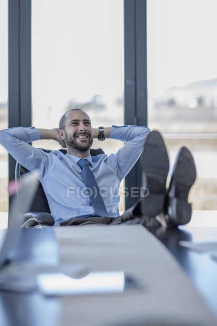 Uomo d'affari sorridente seduto alla sua scrivania con i piedi in su — Foto stock