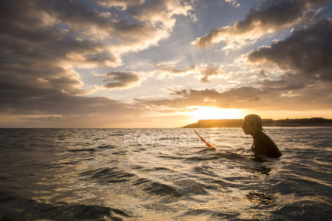 Teenager boy swimming on surfboard in ocean at beautiful sunset — Stock Photo