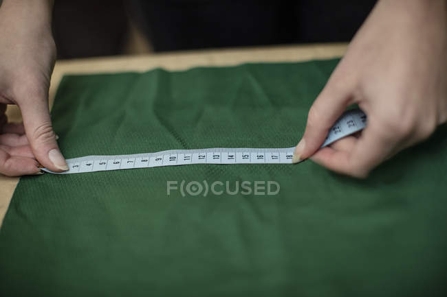 Closeup of woman working with measuring tape in tailor shop — Stock Photo
