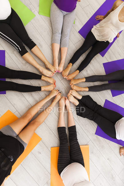 Legs of women in prenatal yoga class sitting together in circle — Stock Photo