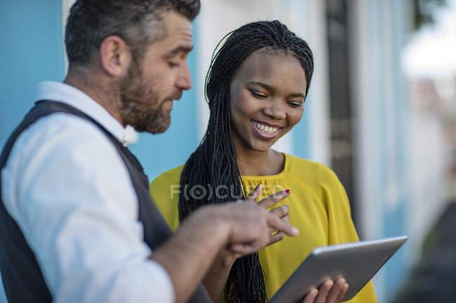 Homme et femme souriante regardant tablette ensemble — Photo de stock