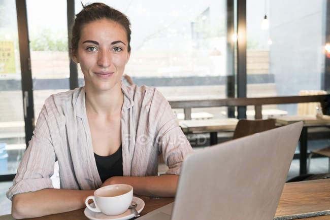 Portrait de jeune femme souriante avec tasse de café et ordinateur portable dans un café — Photo de stock